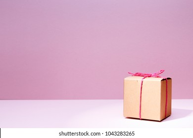 Craft cardboard gift box on the solid pink background. Holiday and gift concept. Horizontal, cold toned