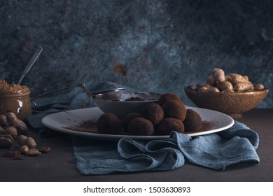 Craft chocolate truffles on plate with cocoa powder and peanuts.