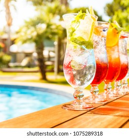 Craft cocktails near the pool. Vacation, summer, holiday, luxury resort concept. Square, toned image, sunset warm hue