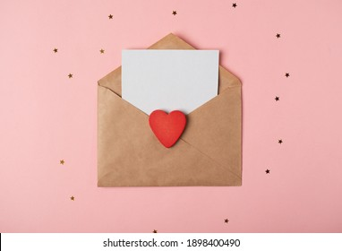 Craft envelope with a blank sheet of paper inside and red wooden heart on the rose background. Romantic love letter for the Valentine's day concept. Space for text. - Shutterstock ID 1898400490