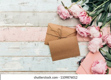 craft envelope and greeting card with peony on wooden background