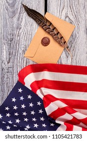 Craft envelope with stamp and American flag. Top view on brown feather, envelope and USA flag, vertical image.