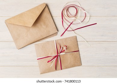 Craft envelopes decoration with red and white ribbons