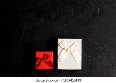 Craft gift box on a black background, decorated with a bow. For birthday, anniversary presents, gift post cards.