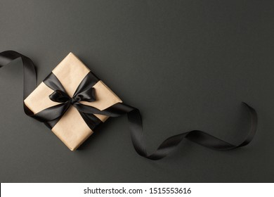Craft gift box on a dark background, decorated with a textured bow and feathers, creating a romantic luxury atmosphere. For birthday, anniversary presents, gift post cards. - Shutterstock ID 1515553616