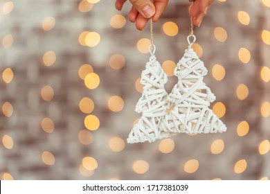Craft gift wicker white Christmas tree pendant in a woman's hand on a background of bokeh Christmas garlands. Christmas tree decoration in the form of a Christmas tree close-up against a brick wall an