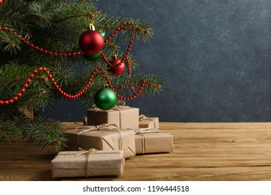 Craft gifts under the tree, on the table, against the wood background. The concept of Christmas and New Year.