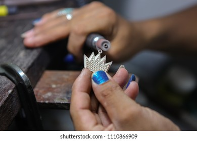 Craft jewelery making. Crown pendant polishing.