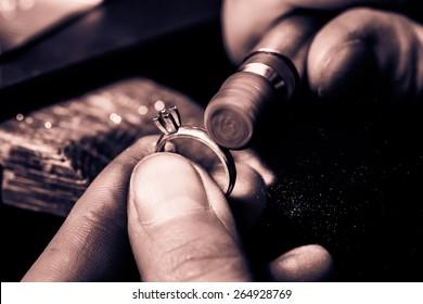 Craft jewelery making. Ring polishing. Macro shot. Monochrome cream tone. Black and white photography.