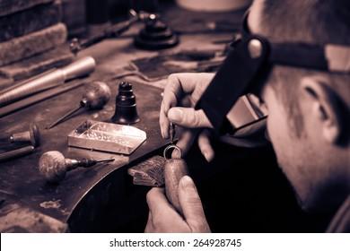 Craft jewelery making.  Ring repairing. Putting the diamond on the ring. Monochrome cream tone. Black and white photography.