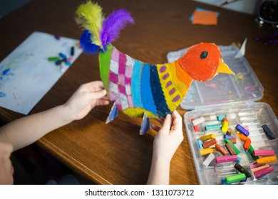 craft with kids. bright bird, cut from cardboard and painted with wax crayons,in the hands of a child. process of creating.