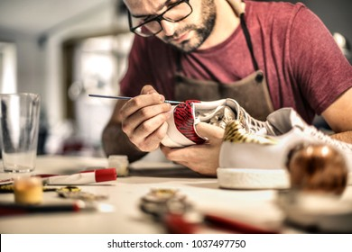 Craft man painting on a pair of shoes