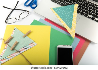 craft materials on desk including scissors and construction paper with glasses cell phone laptop