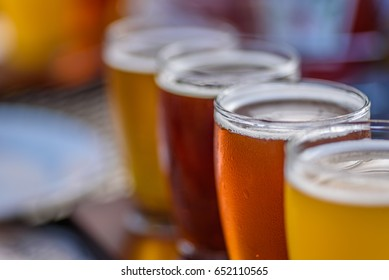 Craft micro brewery beer flight on paddle in sunlight - macro with selective focus