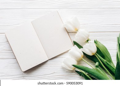 craft notebook, pen and stylish tulips on white wooden rustic background. flat lay with flowers and paper note with space for text. woman working. idea book. fresh start  happy mothers womens day