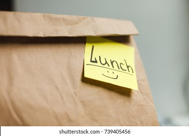 Craft paper bag with funny yellow sticker. Ecological food bag for lunch or food take away delivery, closeup, copy space