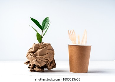 Craft paper coffee cup, green leaves sprout, bark of tree and recycled cutlery top view. Zero waste, eco friendly, natural organic plastic free concept. Earth, biodegradable with copy space.