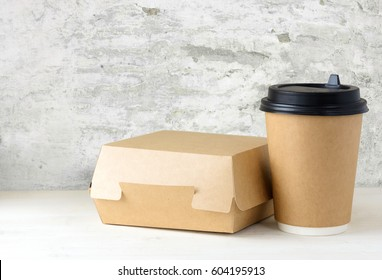 craft paper coffee cup and lunch box on the white table near the white wall with damaged plaster