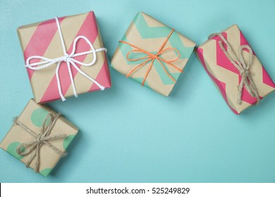 craft paper present boxes tied from rope on blue background, top view