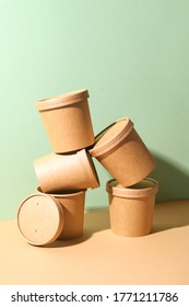 Craft paper soup cups with shadow on green and brown paper background. Take away food. Ecological individual package. Zero Waste.