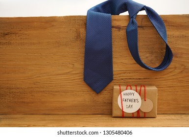 craft paper wrapped gift box with craft paper tag card with mustache on wooden background, top view,  Father's Day concept. tie hang on wooden plank.