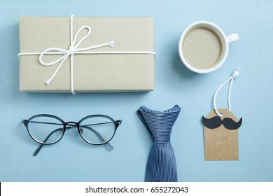 craft paper wrapped gift box, coffee, glasses, necktie and craft paper card tag with mustache on blue background, top view, flat layout as hipster style for Father's Day concept