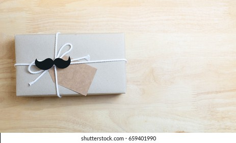 craft paper wrapped gift box with craft paper tag card with mustache on wooden background, top view, flat layout as hipster style for Father's Day concept