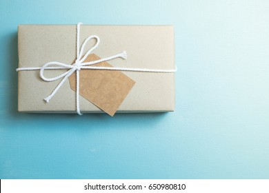 Craft paper wrapped gift with brown craft paper card tag on blue canvas background