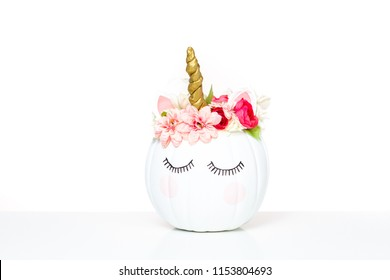 Craft pumpkin painted white and decorated with pink flowers as unicorn on white background.