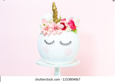 Craft pumpkin painted white and decorated with pink flowers as unicorn on pink background.