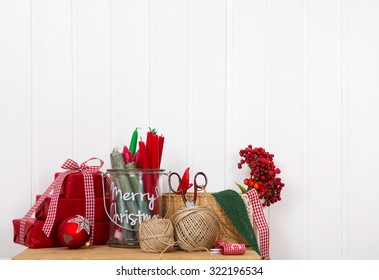Craft supplies for red white christmas gifts on a white wall for a creative background.
