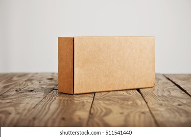 Craft unlabeled cardboard package box presented on stressed brushed wooden table, isolated on white background