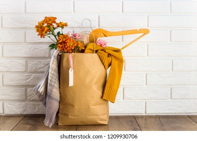 Crafting package with women's purchases on a black Friday, filled with clothes, cosmetics, flowers. Near the white brick wall. Discounts black friday concept