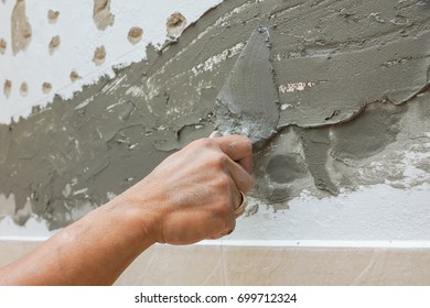 craftman hand using trowel plastering cement mortar wall