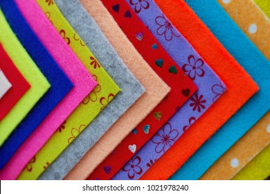 Crafts from colorful felt sheets. Multicolored felt sheets are laid out in a row. View from above. Creativity and needlework of their felt. Sheets of felt for handicrafts.