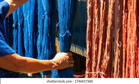 Crafts and craftsmanship. Traditional Isan Thai Cotton indigo weaving. The hand holding the indigo dyeing cloth And natural dyes or bark. Thailand. Selective focus.