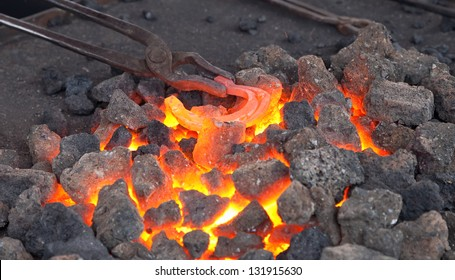 Craftsman blacksmith warming a horseshoe of iron in the fire