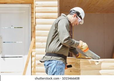Craftsman as carpenter cutting wood with saw