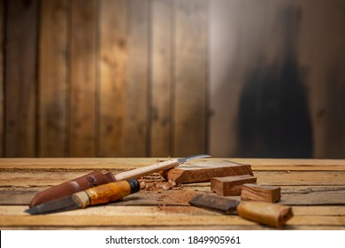 Craftsman carving tools with a chisel  carving knife a piece of dark wood on carpentry workbench