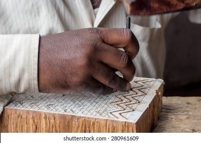 a craftsman carving a wooden printing block for textile block printing