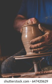 Craftsman ceramist molding the clay in his potter wheel, vintage film effect