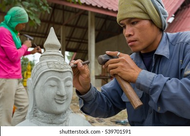 The craftsman concentrate to use the chisel carving the stone Buddha statue at Pakse district, Champasak province, Laos.