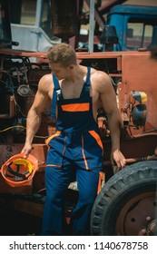 Craftsman concept. Craftsman rest at tractor cabin. Strong craftsman in working uniform at heavy construction machine. Craftsman at backhoe loader.