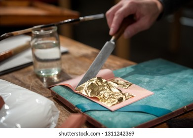 Craftsman cuts an extremely thin gold leaf for the gilding tecnique.