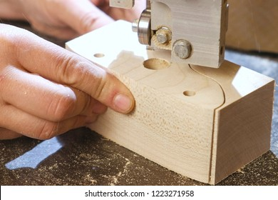 Craftsman is cutting a wood toy cars workpiece from wood with bandsaw. Hands close-up.