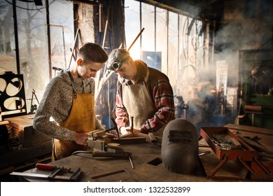 A craftsman in his craft workshop teaches his apprentice how to work on metal pieces