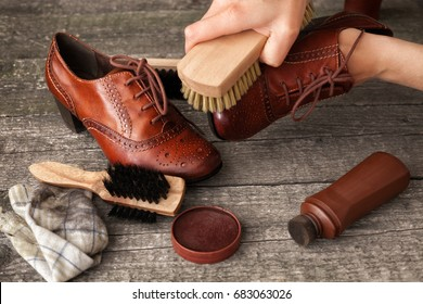 Craftsman holding and cleaning shoe with brush in his workshop