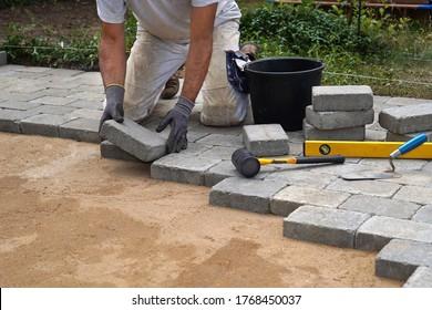A craftsman lays concrete paving stone blocks on sand.