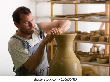 Craftsman making vase from fresh wet clay on pottery wheel.