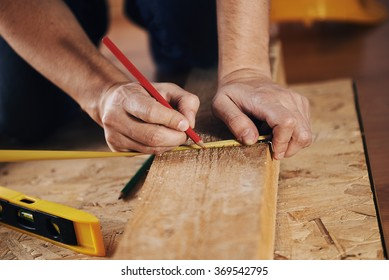 Craftsman measuring wooden plank with ruler on the floor. Concept of diy, woodworking and home renovation.